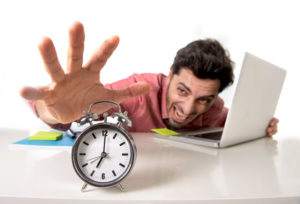 young crazy businessman switching off alarm clock sitting at office desk working with computer laptop in deadline project concept and business stress concept